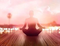 Kvinnan mediterade i soluppgång och strålar av ljus på landskap Arkivbilder