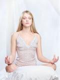 Kvinnan mediterar hemma Arkivfoton