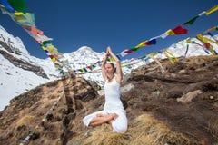 Kvinnan mediterar i bergen nära den Annapurna basläger Royaltyfria Bilder