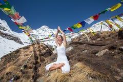 Kvinnan mediterar i bergen nära den Annapurna basläger Royaltyfri Bild