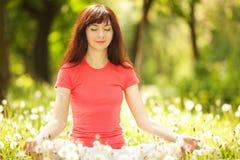 Kvinnan mediterar i parkera Royaltyfria Bilder