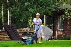 Kvinnan mejar hennes gräsmatta med gräsklipparen arkivfoton