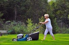 Kvinnan mejar hennes gräsmatta med gräsklipparen royaltyfria foton