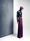 Kvinnan modellerar att posera mycket dramatiskt i en minsta studio ställer in fotografering för bildbyråer