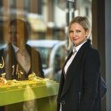 Kvinnan nära shoppar fönstret med juvlar Lyckligt Royaltyfri Foto