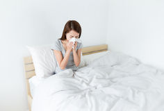 Kvinnan nyser på sängen arkivbilder