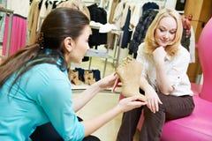 Kvinnan och assistenten på skor shopping royaltyfri bild