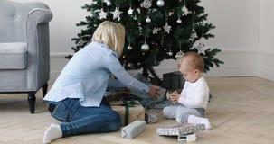 Kvinnan och barnet packar upp gåvan under julgranen arkivfilmer