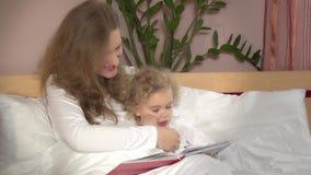 Kvinnan och behandla som ett barn flickaläseboken Fostra och hennes lilla gulliga barn på säng lager videofilmer