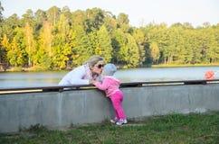 Kvinnan och behandla som ett barn kyssen Arkivfoton