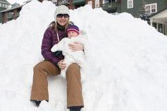 Kvinnan och behandla som ett barn sammanträde på en snödriva Royaltyfri Fotografi