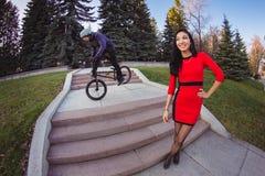 Kvinnan och BMX-cyklisten som gör ett jippo, hoppar Royaltyfri Fotografi