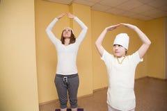 Kvinnan och den tonåriga flickan som gör yoga, övar i idrottshall Arkivfoto