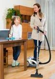 Kvinnan och dottern gör ren huset Royaltyfri Fotografi