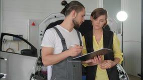 Kvinnan och förlagen nära bearbetar med maskin, besökaren i auto reparation, tjänste- bok stock video