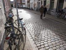 Kvinnan och flickan passerar många parkerade cyklar i mitten av den gamla holländska staden groningen Fotografering för Bildbyråer