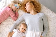 Kvinnan och hennes dotter som den har, vilar på sängen, medan behandla som ett barn har att waken upp royaltyfri foto