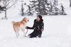 Kvinnan och hennes hund akita att spela in parkerar på snöig dag Vinterconcep royaltyfria bilder