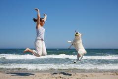 Kvinnan och hunden föder upp labradorbanhoppning på stranden Arkivfoto