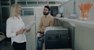Kvinnan och män för arbetare för kontor två har en konversation, och samtidigt skrivar kvinnlign ut någon legitimationshandlingar lager videofilmer
