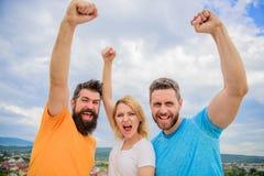 Kvinnan och män ser säker lyckad himmelbakgrund Threesomeställning som är lycklig säkert med lyftta nävar beteende- royaltyfria foton
