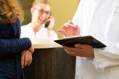 Kvinnan och manipulerar på mottagandet av kliniken Arkivbilder