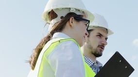 Kvinnan och mannen är de högsta teknikererna av projektet i gröna västar stock video