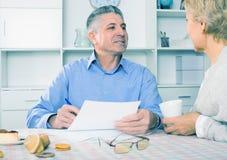 Kvinnan och mannen 51-56 gamla år är diskutera och studera importen Royaltyfri Bild