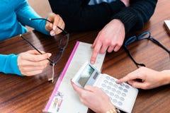 Kvinnan och mannen i optiker shoppar diskutera priset för exponeringsglas arkivfoton