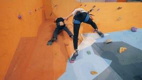 Kvinnan och mannen klättrar en vägg som rymmer händer, nedersta sikt arkivfilmer
