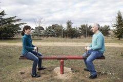 Kvinnan och mannen monterade på en underhållande jämställdhet för gungbräde arkivfoton
