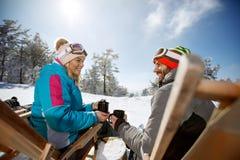Kvinnan och mannen på skidåkning, i sunbed, tycker om med drinken arkivfoton
