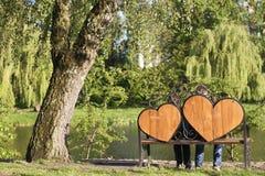 Kvinnan och mannen sitter på en bänk med två stora hjärtor under Arkivfoto