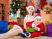 Kvinnan och pojken klädde som Santa Claus Royaltyfri Foto