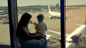 Kvinnan och pojken ser landningsbanan tillsammans i flygplatsen, slut upp En familj väntar på ett flyg, medan hålla ögonen på hyv stock video
