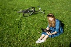 Kvinnan och tappning cyklar, bärbara datorn, grön gräsmatta, sommar Rött hårflickasammanträde på gräset utanför en skola som rymm Fotografering för Bildbyråer