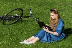 Kvinnan och tappning cyklar, bärbara datorn, grön gräsmatta, sommar Rött hårflickasammanträde på gräset utanför en skola som rymm Royaltyfri Bild
