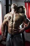 Kvinnan omfamnar passionately den muskulösa mannen i idrottshallen Arkivbilder