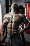 Kvinnan omfamnar passionately den muskulösa mannen i idrottshallen Royaltyfria Foton