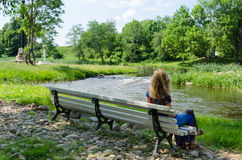 Kvinnan på bänk beundrar den snabba strömmen för flödesflodvatten royaltyfri bild