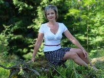 Kvinnan på bakgrunden av skogen royaltyfri fotografi