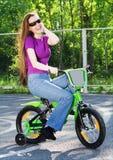 Kvinnan på barns cykel Royaltyfria Foton