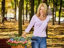 Kvinnan på cykeln med blommakorghöst parkerar utomhus- Royaltyfri Bild