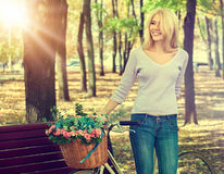Kvinnan på cykeln med blommakorgsommar parkerar tonad bild Royaltyfri Foto
