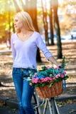 Kvinnan på cykeln med blommakorgsommar parkerar utomhus- Arkivfoto