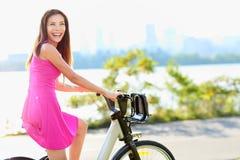 Kvinnan på cykeln som cyklar i stad, parkerar Fotografering för Bildbyråer