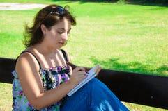 Kvinnan på en bänk skriver in i hennes notepad royaltyfri fotografi