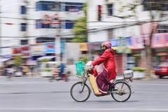 Kvinnan på en elektrisk cykel transporterar livsmedel, Shanghai, Kina Royaltyfria Bilder