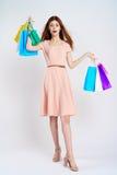 Kvinnan på en vit bakgrund rymmer pappers- påsar, shopping, shopping, underhållning Arkivbilder