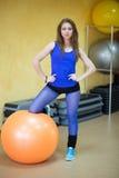 Kvinnan på idrottshallen med pilates klumpa ihop sig Royaltyfri Bild